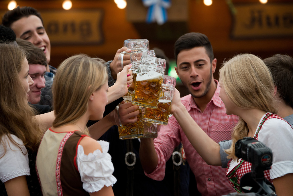 Description of . Visitors in Bavarian style clothes raise their glasses after getting their first Oktoberfest beer in the Schottenhamel-tent at the Oktoberfest 2013 beer festival at Theresienwiese on September 21, 2013 in Munich, Germany. (Photo by Joerg Koch/Getty Images)