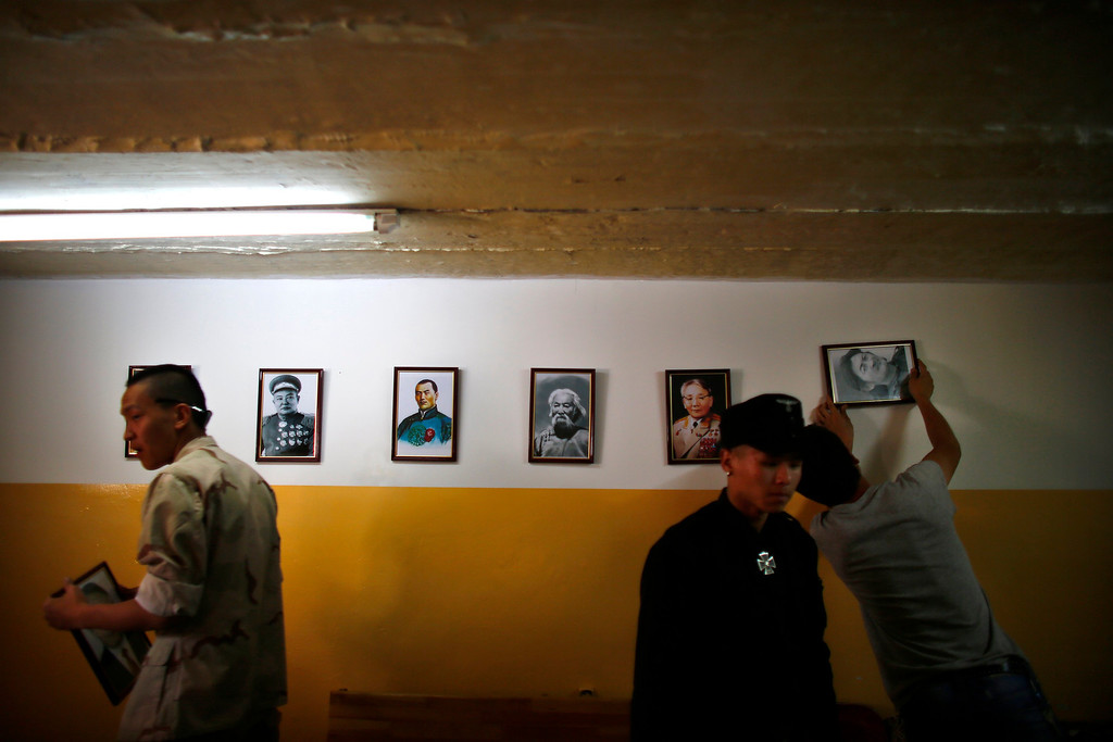 Description of . Members of the Mongolian neo-Nazi group Tsagaan Khass hang up portraits of Mongolian heroes at the group's headquarters in Ulan Bator June 24, 2013. The group has rebranded itself as an environmentalist organisation fighting pollution by foreign-owned mines, seeking legitimacy as it sends Swastika-wearing members to check mining permits. Over the past years, ultra-nationalist groups have expanded in the country and among those garnering attention is Tsagaan Khass, which has recently shifted its focus from activities such as attacks on women it accuses of consorting with foreign men to environmental issues, with the stated goal of protecting Mongolia from foreign mining interests. This ultra-nationalist group was founded in the 1990s and currently has 100-plus members. Picture taken June 24, 2013. REUTERS/Carlos Barria