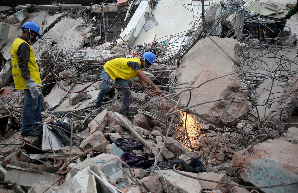 Description of . Workers toil in a collapsed garment factory building on Tuesday, April 30, 2013 in Savar, near Dhaka, Bangladesh. Emergency workers hauling large concrete slabs from the collapsed eight-story building said Tuesday they expect to find many dead bodies when they reach the ground floor. (AP Photo/Wong Maye-E)