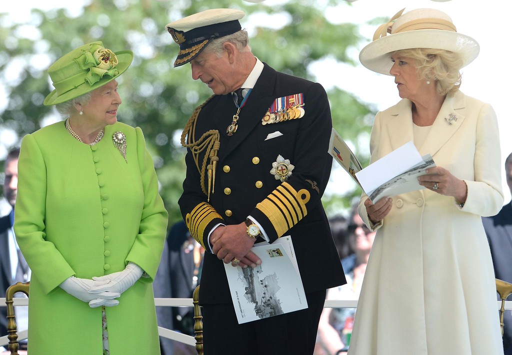 Description of . Britain's Queen Elizabeth II (L), Britain's Prince Charles, Prince of Wales (C) and his wife Camilla, the Duchess of Cornwall Camilla (R) attend a bi-national France-UK D-Day commemoration ceremony at the British War Cemetery of Bayeux, on June 6, 2014, marking the 70th anniversary of the World War II Allied landings in Normandy. AFP PHOTO / POOL / THOMAS  BREGARDIS/AFP/Getty Images