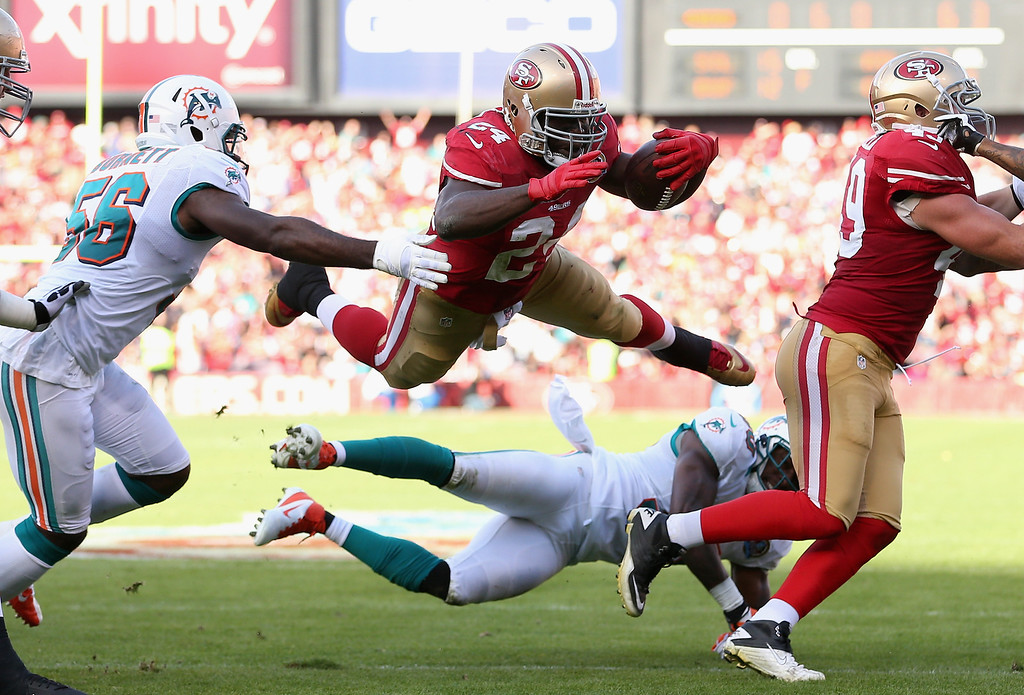 Description of . SAN FRANCISCO, CA - DECEMBER 09: Anthony Dixon #24 of the San Francisco 49ers leaps over Chris Clemons #30 of the Miami Dolphins at Candlestick Park on December 9, 2012 in San Francisco, California.  (Photo by Ezra Shaw/Getty Images)