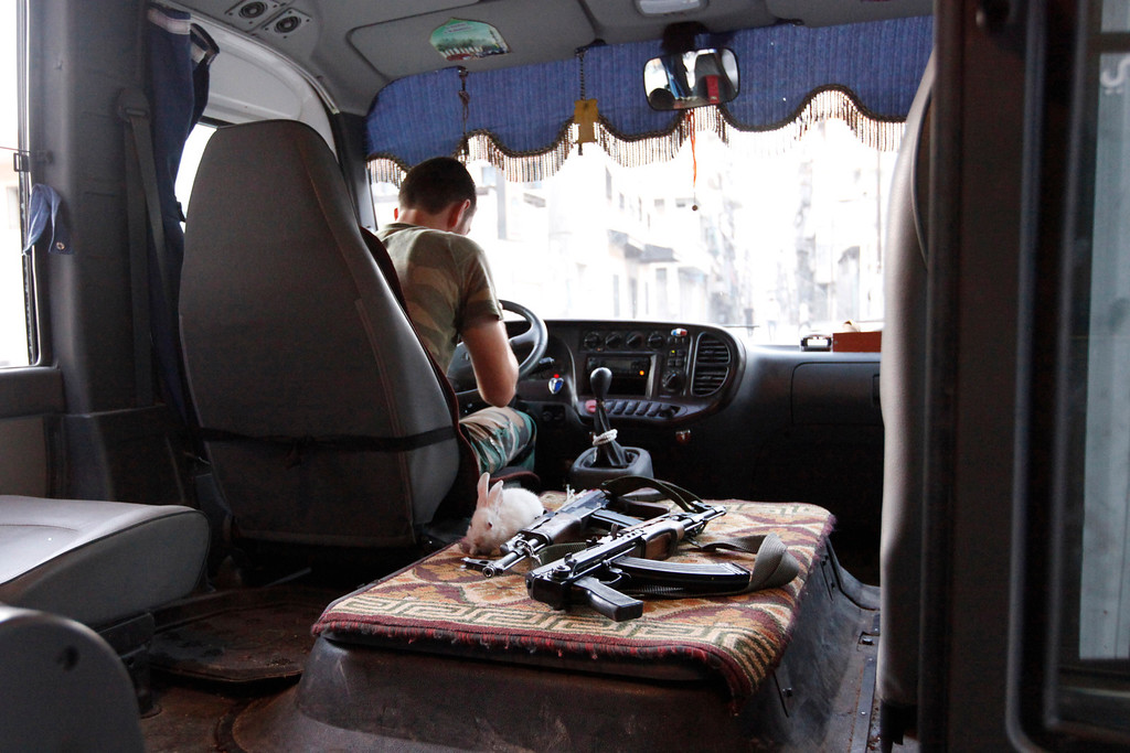 Description of . A rabbit is pictured next to weapons in a Free Syrian Army bus in Bustan Al-Basha district in Aleppo September 18, 2012. REUTERS/Zain Karam