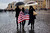 A woman walks across St Peter's Square in an American flag as others wait for smoke to emanate from the chimney on the roof of the Sistine Chapel which will indicate whether or not the College of Cardinals have elected a new Pope on March 13, 2013 in Vatican City, Vatican. (Photo by Spencer Platt/Getty Images)
