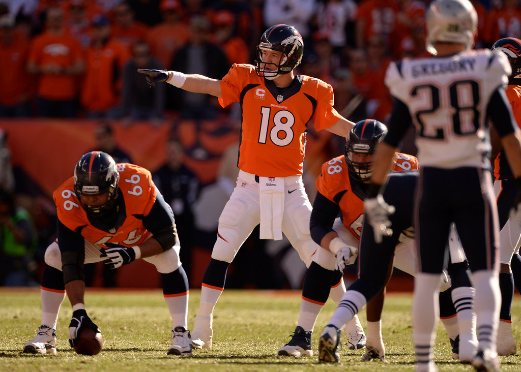 Description of . Denver Broncos quarterback Peyton Manning (18) runs the offense during the first quarter. The Denver Broncos vs. The New England Patriots in an AFC Championship game  at Sports Authority Field at Mile High in Denver on January 19, 2014. (Photo by John Leyba/The Denver Post)