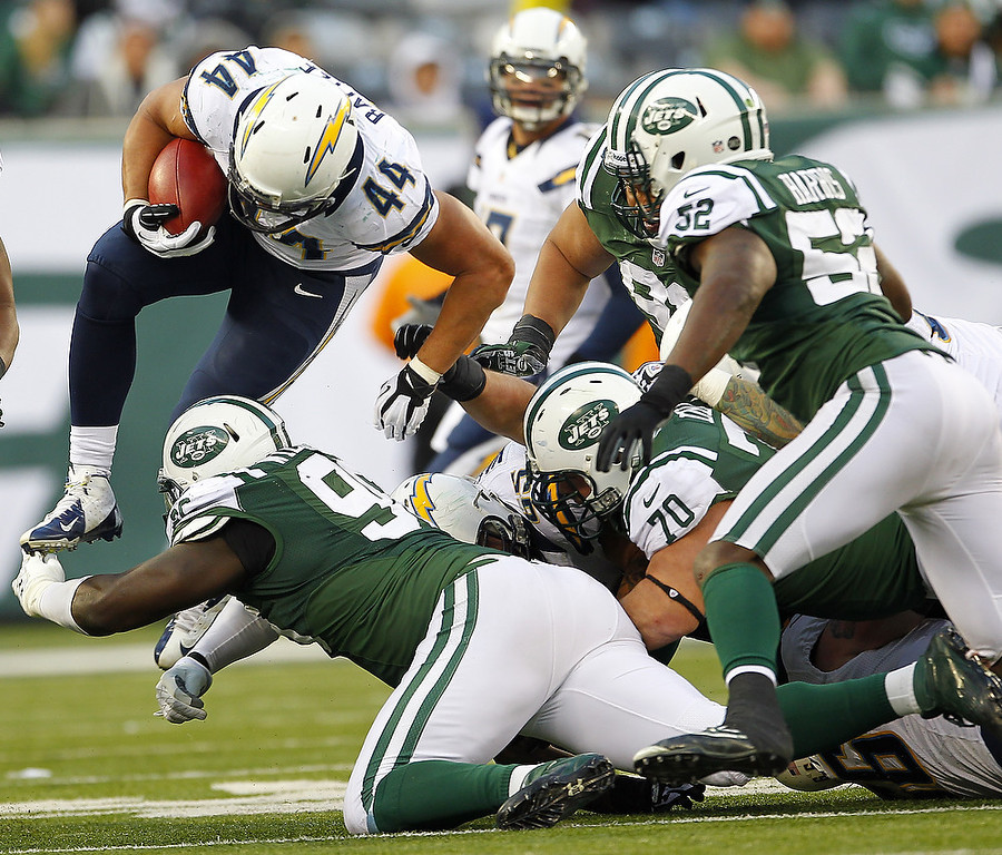 Description of . Running back Jackie Battle #44 of the San Diego Chargers leaps over Muhammad Wilkerson #96 of the New York Jets during the second half at MetLife Stadium on December 23, 2012 in East Rutherford, New Jersey. The Chargers defeated the Jets 27-17. (Photo by Rich Schultz /Getty Images)