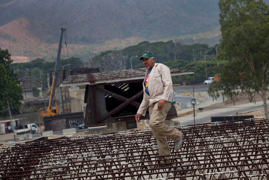 Description of . In this April 8, 2013 photo, construction worker Anselmo Mendoza, 46, walks through rows of rebar at a bridge construction site in San Diego, Venezuela. Outside Venezuela's capital, power outages, food shortages and unfinished projects abound; important factors heading into Sunday's election to replace Venezuela's late President Hugo Chavez, who died last month after a long battle with cancer. Maduro, Chavez's hand-picked successor, has generally avoided references to public works on the campaign trail, although on a stop this week in Apure state, he did apologize for a delayed highway extension, maternity hospital and bridge. (AP Photo/Ramon Espinosa)