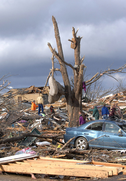 Description of . A mattress is wrapped around a stripped tree in Washington, Ill., Sunday, Nov. 17, 2013. Intense thunderstorms and tornadoes swept across the Midwest, causing extensive damage in several central Illinois communities while sending people to their basements for shelter. (AP Photo/The Pantagraph, Steve Smedley)