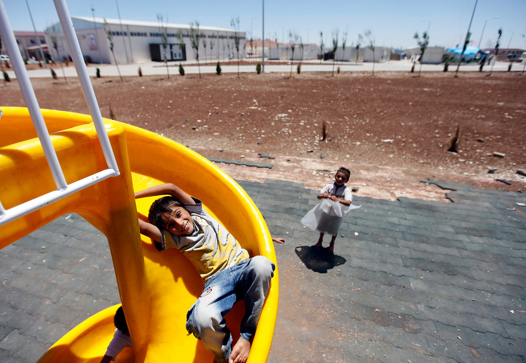 Description of . A Syrian refugee girl plays in a playground at a refugee camp named