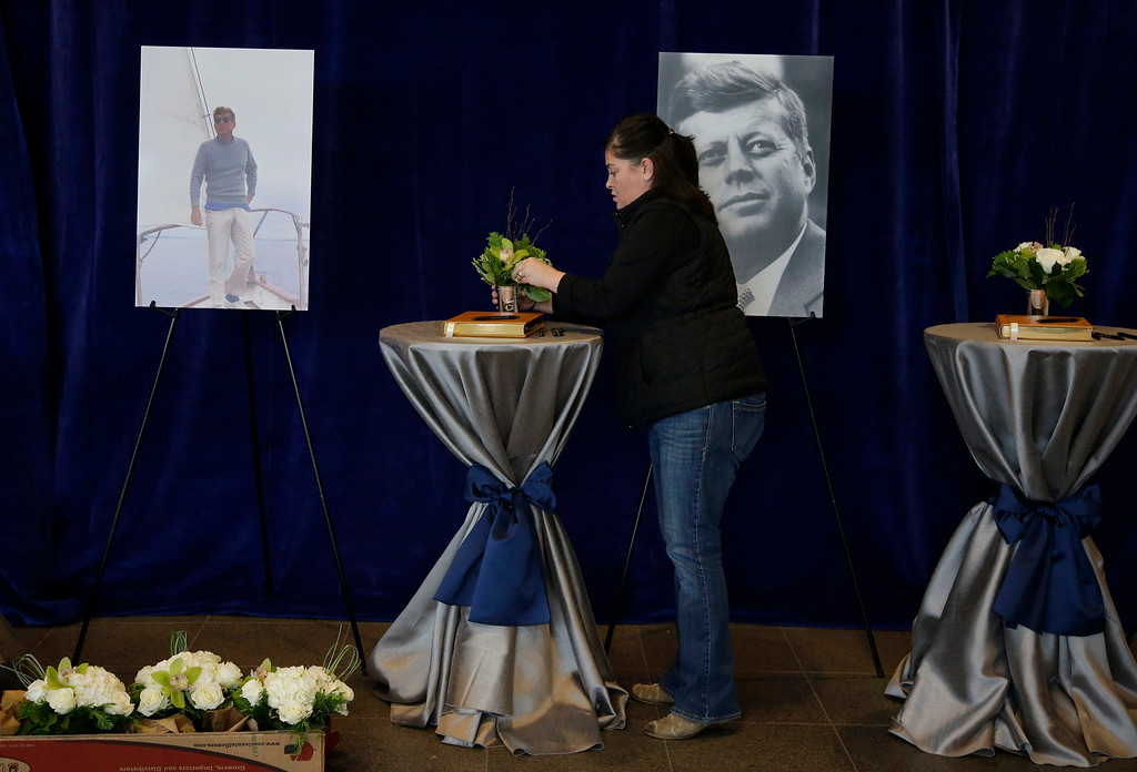 Description of . A woman arranges flowers at the sign in tables in the John F. Kennedy Presidential Library and Museum before visitors arrive Friday Nov. 22, 2013 in Boston. Kennedy, the 35th President of the United States, was assassinated in Dallas 50 years ago today. (AP Photo/Stephan Savoia)