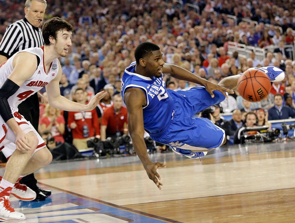 Description of . Kentucky forward Alex Poythress (22) saves the ball from going out as Wisconsin forward Frank Kaminsky (44) defends during the second half of the NCAA Final Four tournament college basketball semifinal game Saturday, April 5, 2014, in Arlington, Texas. (AP Photo/Eric Gay)