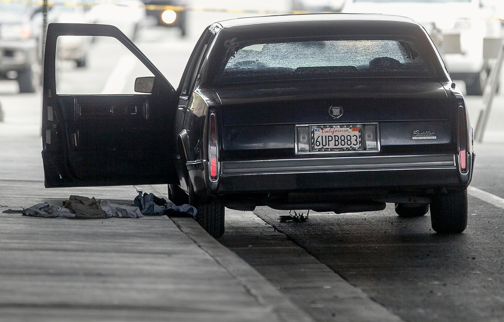 . A vehicle riddle with bullet holes is part of  a crime scene on Red Hills Ave. under the 5 Interstate in Tustin, Calif., Tuesday, Feb. 19, 2013. (AP Photo/Damian Dovarganes)