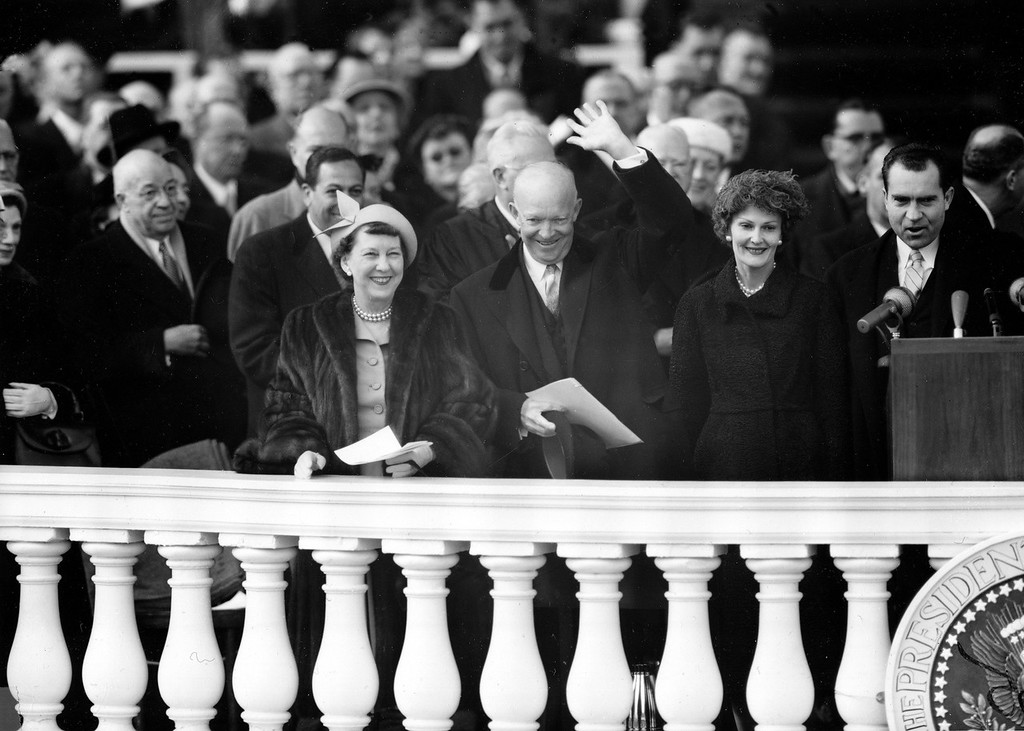Description of . U.S. President Dwight Eisenhower acknowledges applause as he stands on the Capitol inaugural stand with first lady Mamie Eisenhower, left, in Washington, D.C., Jan. 21, 1957. Vice President Richard Nixon is at far right, with his wife, Pat, second from right. (AP Photo)