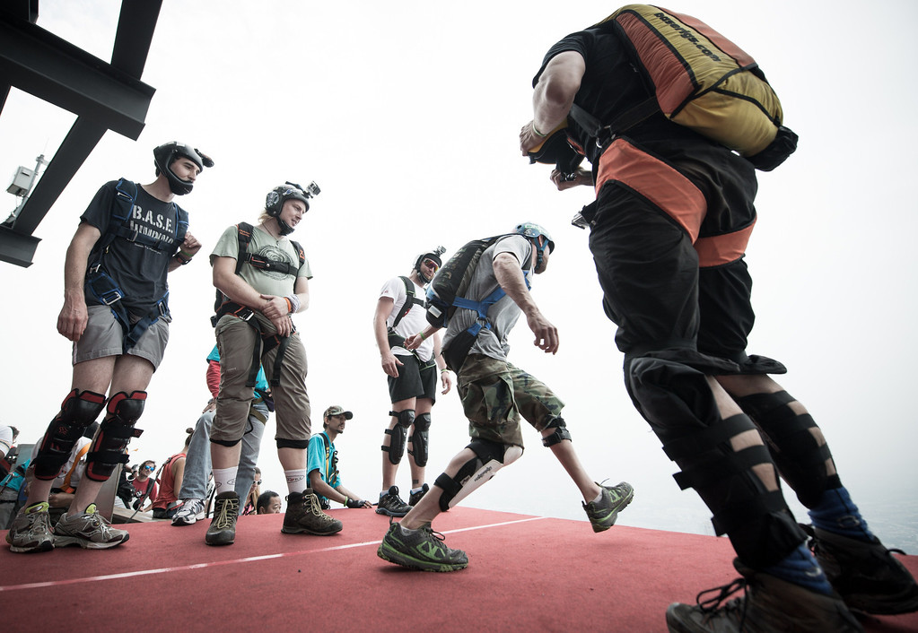 Description of . Base jumper Sean Thomas Chuma (2nd,R) from the US leaps from the 300-meters Open Deck of the Malaysia's landmark Kuala Lumpur Tower during the International Tower Jump in Kuala Lumpur on September 27, 2013.  AFP PHOTO / MOHD RASFAN/AFP/Getty Images