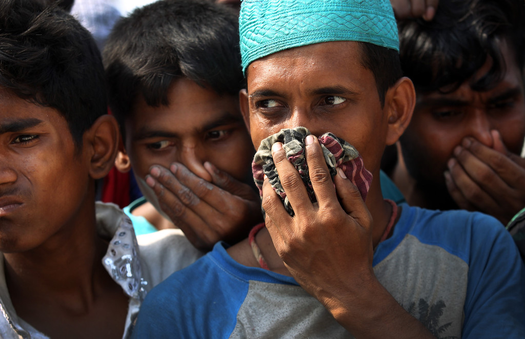 Description of . People cover their noses to block out the smell of decomposing bodies as a truck transporting unclaimed bodies from the garment factory building that collapsed last week arrives for a mass burial, Wednesday, May 1, 2013, in Dhaka, Bangladesh.    (AP Photo/Wong Maye-E)