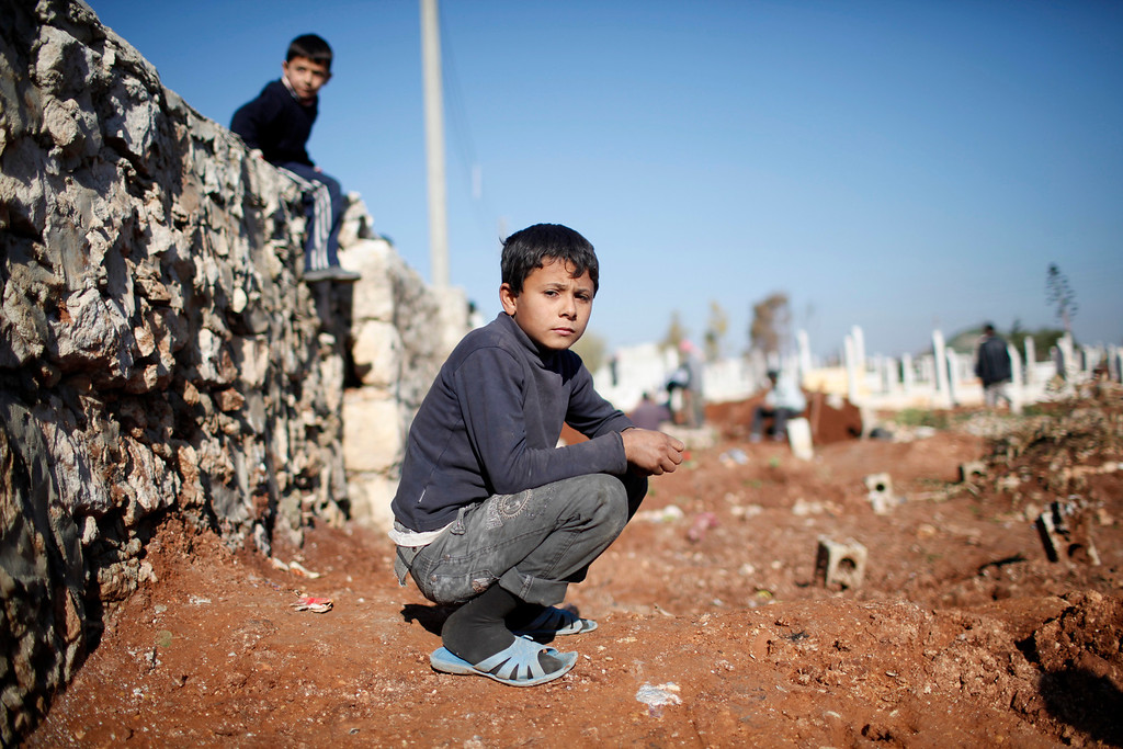 Description of . A child watches men dig graves for future casualties of Syria's civil conflict at Sheikh Saeed cemetery in Azaz city, north of Aleppo December 30, 2012.    REUTERS/Ahmed Jadallah