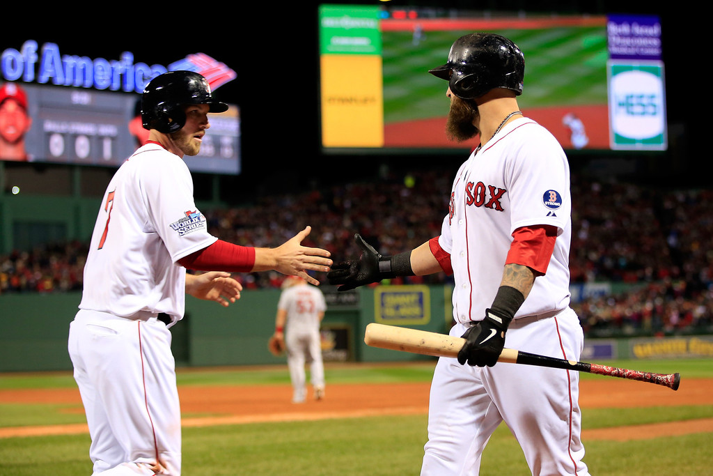 Description of . Stephen Drew #7 of the Boston Red Sox celebrates with Mike Napoli #12 after scoring in the second inning on a hit by Dustin Pedroia #15 against the St. Louis Cardinals during Game One of the 2013 World Series at Fenway Park on October 23, 2013 in Boston, Massachusetts.  (Photo by Jamie Squire/Getty Images)