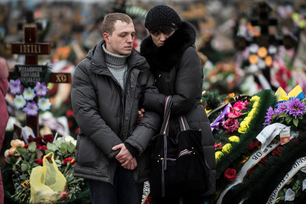 Description of . Relatives of Alexander Demyanenko, a victim of Saturday's shelling, stand near a grave during funerals in Mariupol, Ukraine, on Monday Jan. 26, 2015. At least 5,100 people have been killed in eastern Ukraine since fighting began in April, but violence this week was the most intense since a cease-fire deal was signed in September. (AP Photo/Evgeniy Maloletka)