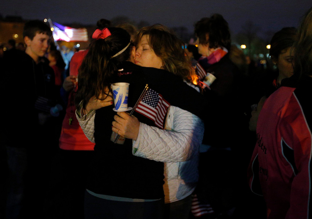 Description of . Local residents hug at a candle light vigil in the Dorchester neighborhood of Boston, Massachusetts April 16, 2013 where eight-year-old Boston Marathon bombing victim Martin Richard lived. A Little League baseball player, Martin lived in the blue Victorian house in working-class Dorchester - a Boston neighborhood dotted with
