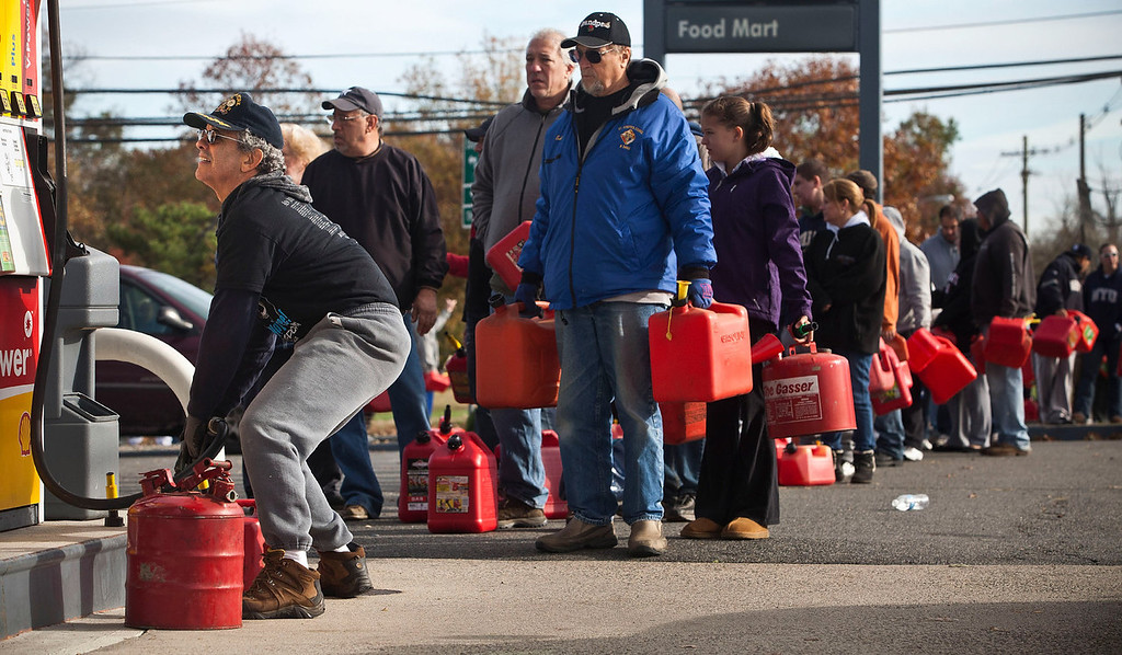 . A man fills up jerry cans with gasoline as others wait in line on November 1, 2012 in Hazlet township, New Jersey. United States. Superstorm Sandy, which has left millions without power or water, continues to effect business and daily life throughout much of the eastern seaboard.  (Photo by Andrew Burton/Getty Images)
