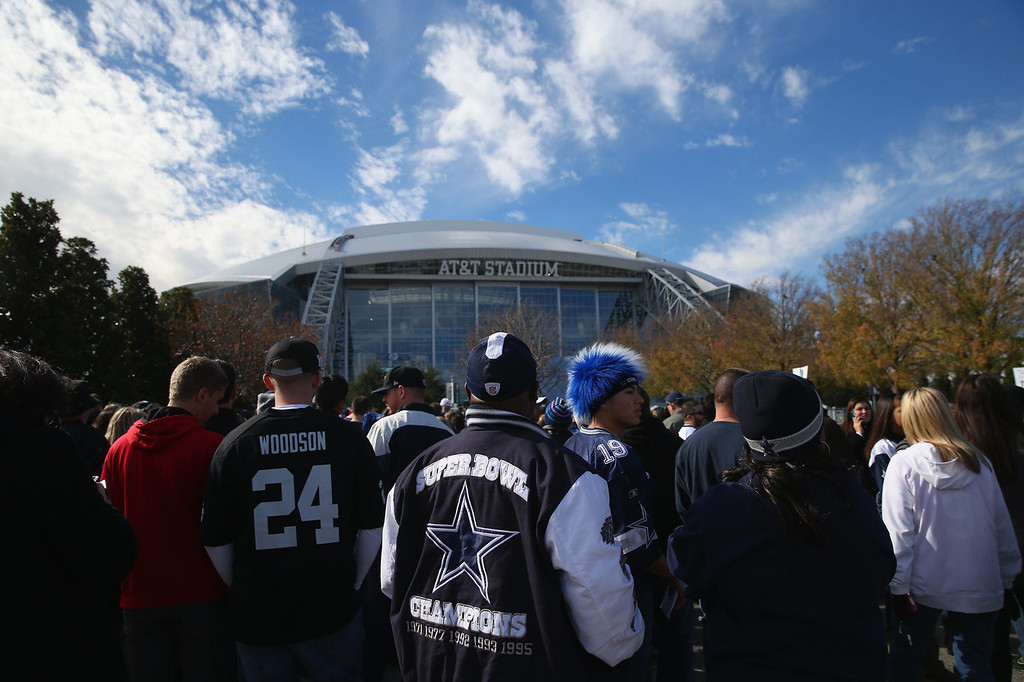 Description of . NFL fans stand in line before a game between the Oakland Raiders and the Dallas Cowboyson November 28, 2013 in Arlington, Texas.  (Photo by Ronald Martinez/Getty Images)