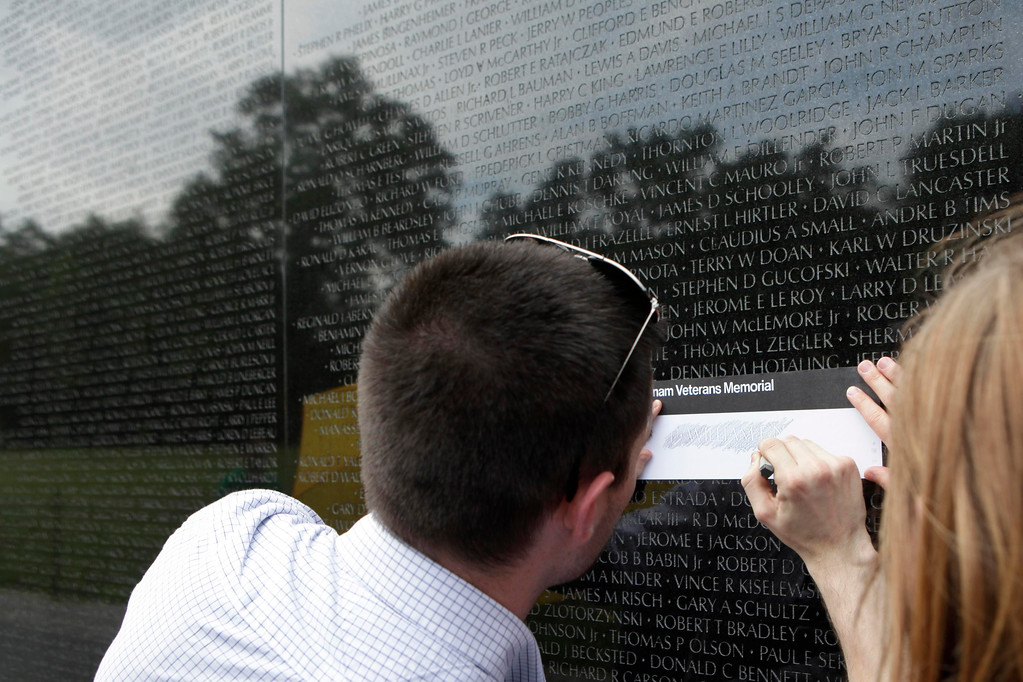 Description of . A visitor does a pencil rubbing of a name on the Vietnam Veterans Memorial wall, etched with the names of more than 58,000 U.S. servicemen and women who died in the war, in Washington May 23, 2013. Memorial Day falls on May 27 this year.  REUTERS/Yuri Gripas