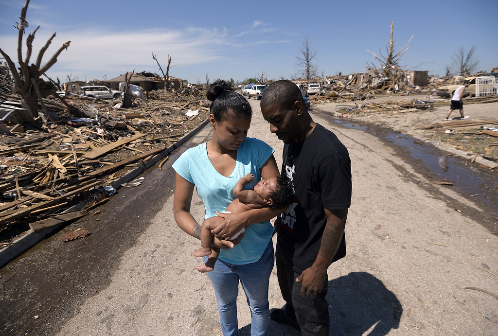 Description of . Tornado survivor Arlisha Hall holds her 2-month-old daughter Akai Hall as she along with her husband Wyatt Hall walk back to their home on May 22, 2013 in Moore, Oklahoma. As rescue efforts in Oklahoma wound down, residents turned to the daunting task of rebuilding a US heartland community shattered by a vast tornado that killed at least 24 people. The epic twister, two miles (three kilometers) across, flattened block after block of homes as it struck mid-afternoon on May 20, hurling cars through the air, downing power lines and setting off localized fires in a 45-minute rampage. JEWEL SAMAD/AFP/Getty Images