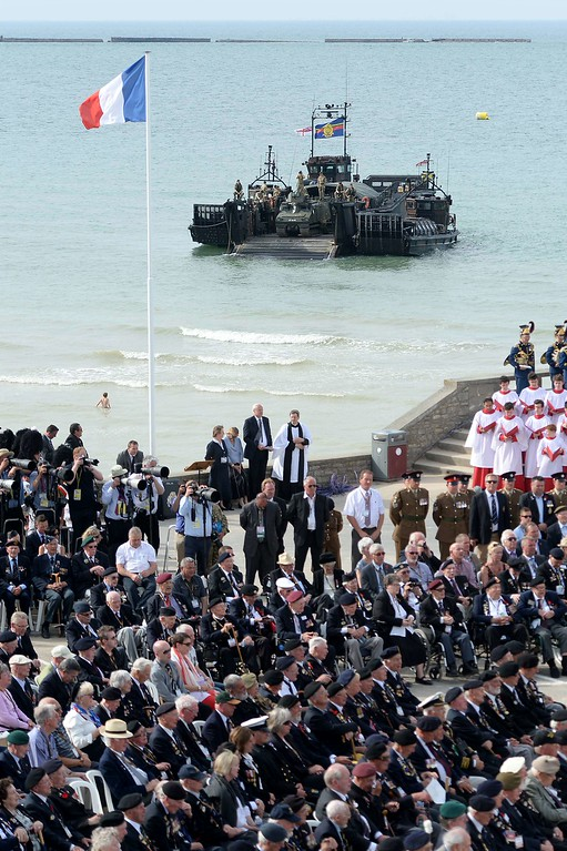 Description of . WWII veterans and officials attend a a D-Day commemoration ceremony for veterans in Arromanches-les-Bains, Normandy, on June 6, 2014, marking the 70th anniversary of the World War II Allied landings in Normandy. AFP PHOTO / THOMAS BREGARDIS/AFP/Getty Images