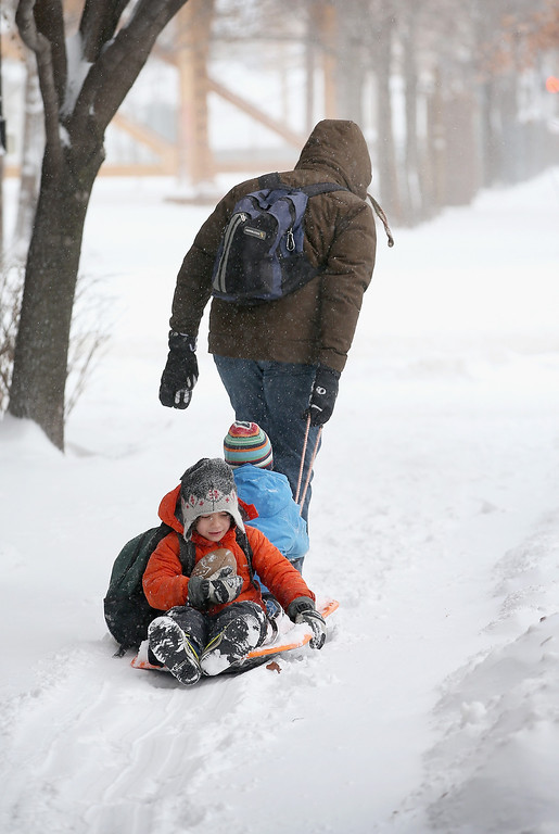 Description of . Children get a ride down a snow-covered sidewalk the Wicker Park neighborhood on February 5, 2014 in Chicago, Illinois.  (Photo by Scott Olson/Getty Images)