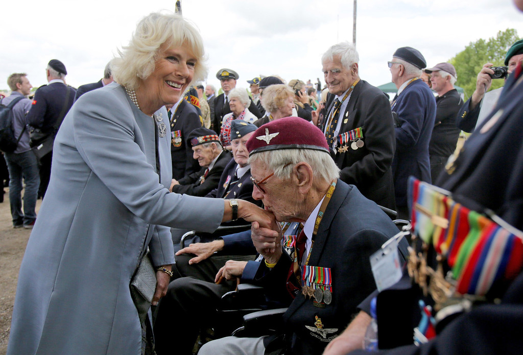 Description of . British Normandy Veteran Raymond Shuck, who was a paratrooper on D-Day kisses the hand of Camilla, Duchess of Cornwall as she meets veterans near Pegasus Bridge (Also known as the Bénouville Bridge - The taking of the Bridge was an important strategic victory) during D-Day Commemorations on June 5, 2014 in Ranville, near Caen in Normandy, France.  (Photo by Matt Cardy/Getty Images)
