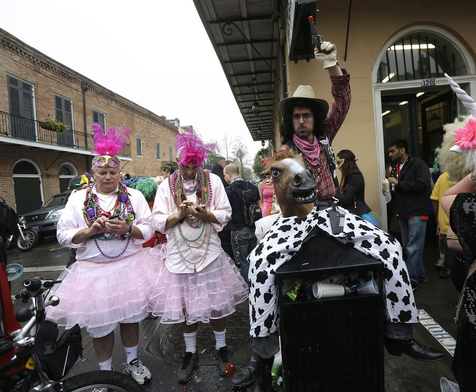 Description of . A man dressed as a cowboy holding a horse head,  sits on a trash can next to two men in pink dresses sending text messages during Mardi Gras in the French Quarter of New Orleans, Tuesday, Feb. 12, 2013.  Despite threatening skies, the Mardi Gras party carried on as thousands of costumed revelers cheered glitzy floats with make-believe monarchs in an all-out bash before Lent.   Crowds were a little smaller than recent years, perhaps influenced by the forecast of rain. Still, parades went off as scheduled even as a fog settled over the riverfront and downtown areas. (AP Photo/Gerald Herbert)