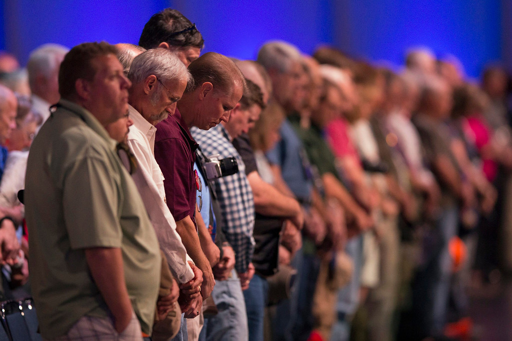 Description of . National Rifle Association members bow their heads in prayer before the start of the Annual Meeting of Members in Houston, Texas on May 4, 2013. Organizers expect some 70,000 attendees at the 142nd NRA Annual Meetings & Exhibits in Houston, which began on Friday and continues through Sunday. REUTERS/Adrees Latif