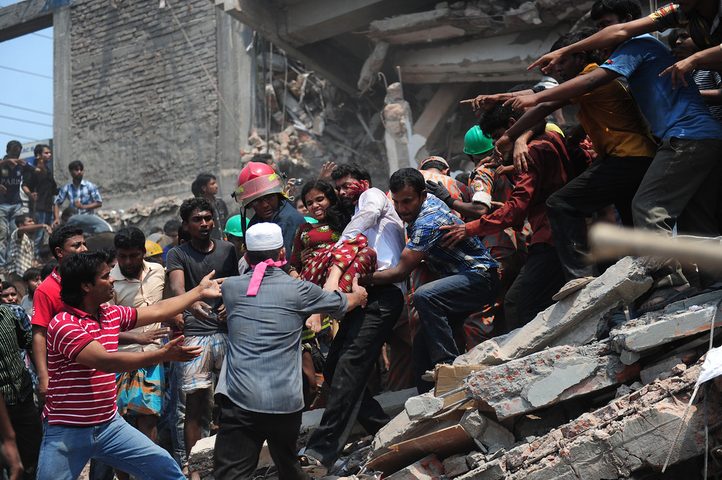Description of . Bangladeshi volunteers evacuate an injured garment worker after an eight-story building collapsed in Savar, on the outskirts of Dhaka, on April 24, 2013.  AFP PHOTO/Munir UZ ZAMAN/AFP/Getty Images