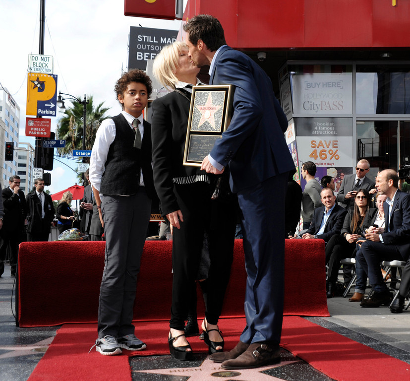 Description of . Actor Hugh Jackman, right, and his wife, actress Deborra-Lee Furness, share a kiss, while their son, Oscar Jackman, looks on at Hugh Jackman's star ceremony at the Hollywood Walk of Fame on Thursday, Dec. 13, 2012, in Los Angeles. (Photo by Dan Steinberg/Invision/AP)