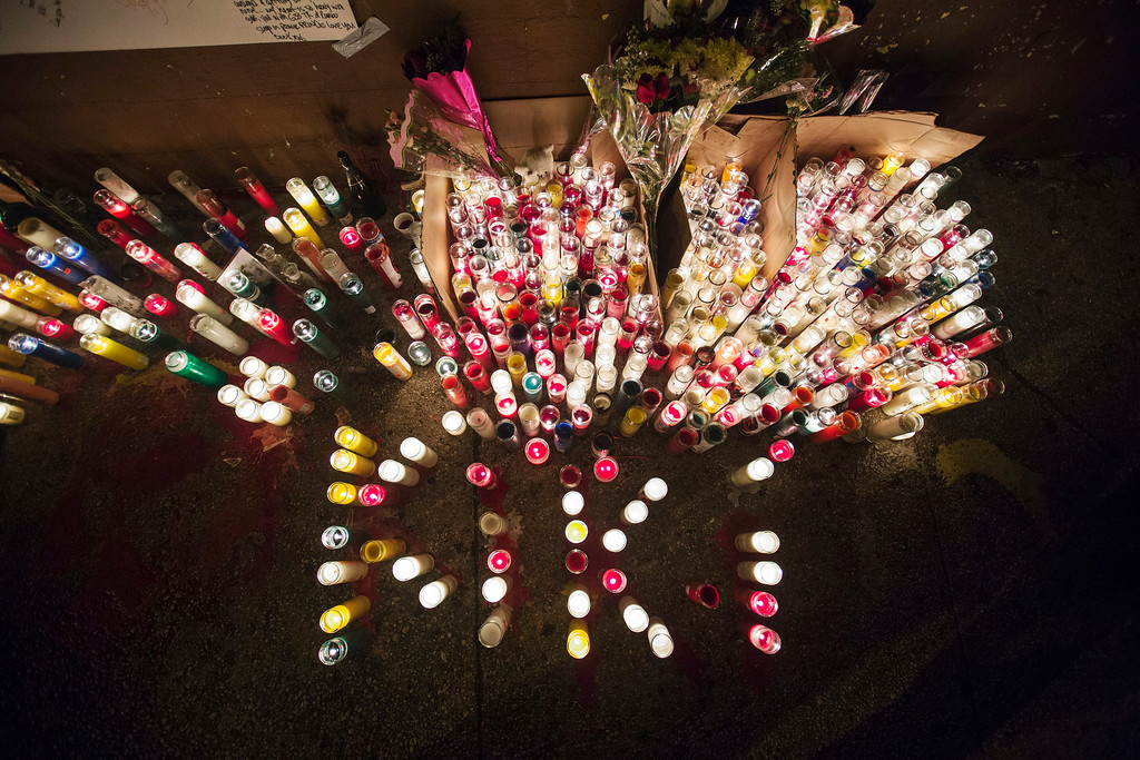 Description of . Candles stand lit on a street corner making up a memorial for 16-year-old Kimani