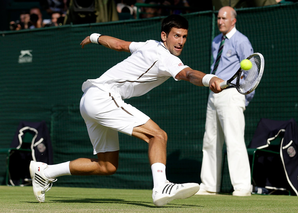 Description of . Novak Djokovic of Serbia plays a return to Andy Murray of Britain during the Men's singles final match at the All England Lawn Tennis Championships in Wimbledon, London, Sunday, July 7, 2013. (AP Photo/Anja Niedringhaus, Pool)