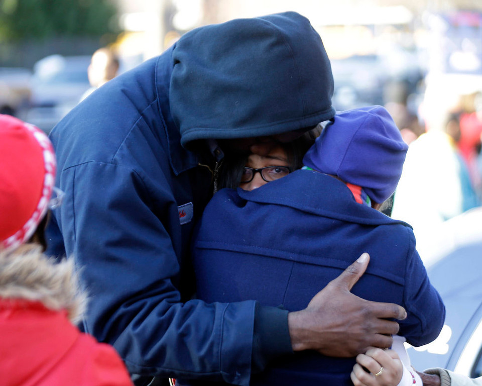 Description of . A man and a woman are reunited with a child a child after after a shooting at an Price Middle school in Atlanta Thursday, Jan. 31, 2013. A 14-year-old boy was wounded outside the school Thursday afternoon and a fellow student was in custody as a suspect, authorities said. No other students were hurt. (AP Photo/John Bazemore)