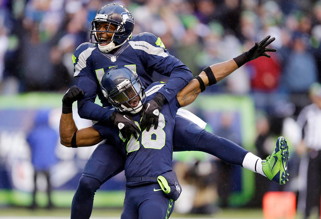 Description of . Seattle Seahawks' Byron Maxwell, top, leaps on the back of Walter Thurmond after Thurmond intercepted and scored against the Minnesota Vikings in the second half of an NFL football game Sunday, Nov. 17, 2013, in Seattle. (AP Photo/Ted S. Warren)