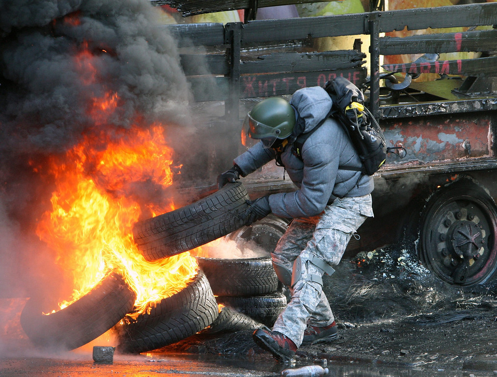 Description of . An protester throws tires on a barricade during the continuing protest in downtown Kiev, Ukraine, 18 February 2014.   EPA/IGOR KOVALENKO