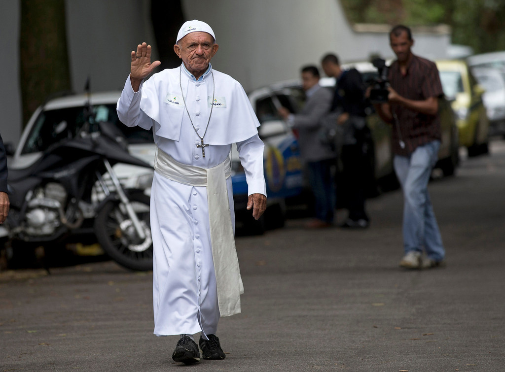 Description of . Roque Steves, dressed in the likeness of the Pope, waves to members of security and the press as he arrives to the Sumare residence where Pope Francis is staying in Rio de Janeiro, Brazil, Tuesday, July 23, 2013. Steves said he is a social worker who caters to the poor, and his outfit was his way of calling attention to charity work. Francis is in Brazil for World Youth Day, a church event that takes place about every three years and brings together young Catholics from around the world. (AP Photo/Silvia Izquierdo)