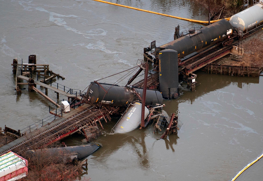 Description of . Derailed freight train cars lay in water in Paulsboro, N.J., Friday, Nov. 30, 2012. People in three southern New Jersey towns were told Friday to stay inside after the freight train derailed and several tanker cars carrying hazardous materials toppled from a bridge and into a creek. (AP Photo/Cliff Owen)