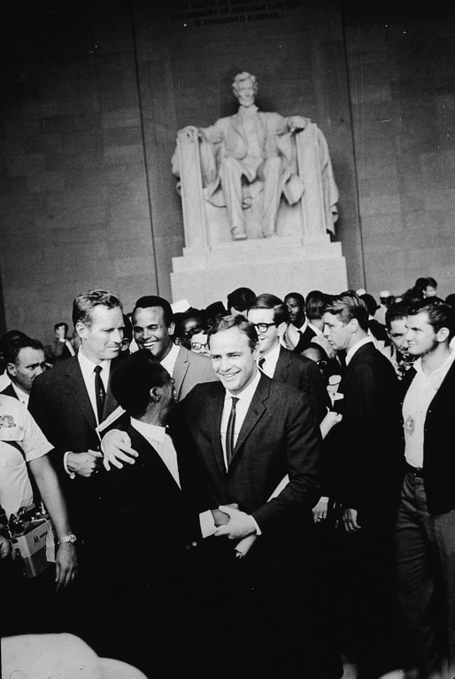 Description of . American actor Marlon Brando (1924 - 2004) stands with his arm around poet James Baldwin, surrounded by actors Charlton Heston (L), Harry Belafonte and others gathered at the Lincoln Memorial during the Civil Rights March on Washington, D.C., August 28, 1963. (Photo by Hulton Archive/Getty Images)
