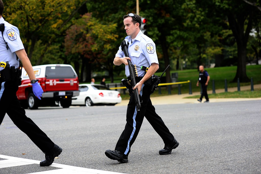 Description of . Police react after shots fired were reported near 2nd Street NW and Constitution Avenue on Capitol Hill in Washington, DC, on October 3, 2013.  The US Capitol was placed on security lockdown Thursday after shots were fired outside the complex, senators said.