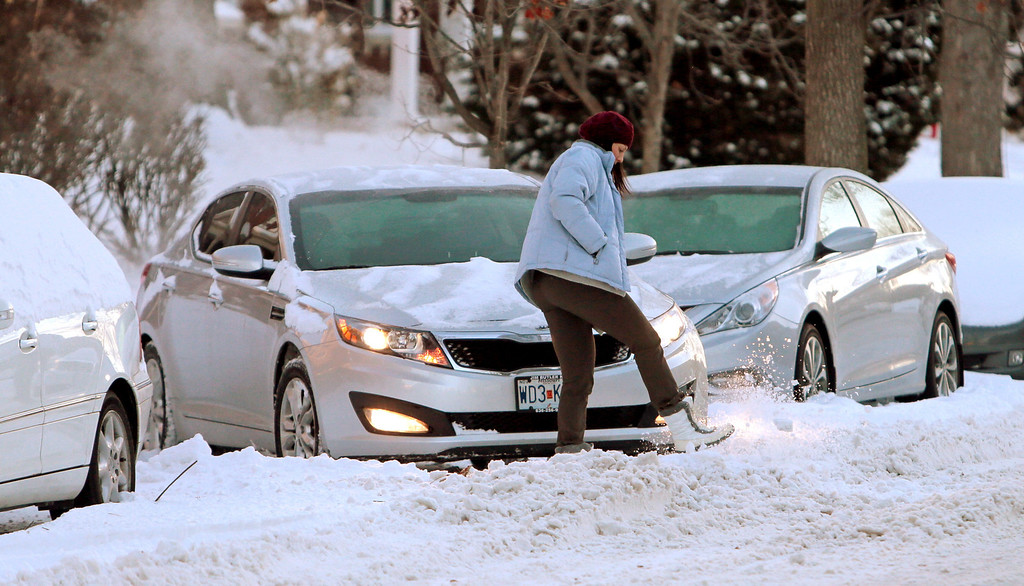 Description of . Sarah Smith tries to kick a clear path in the snow to free her trapped car on Tuesday, Jan. 7, 2014, outside of her apartment along the 5100 block of Waterman Blvd. in St. Louis.