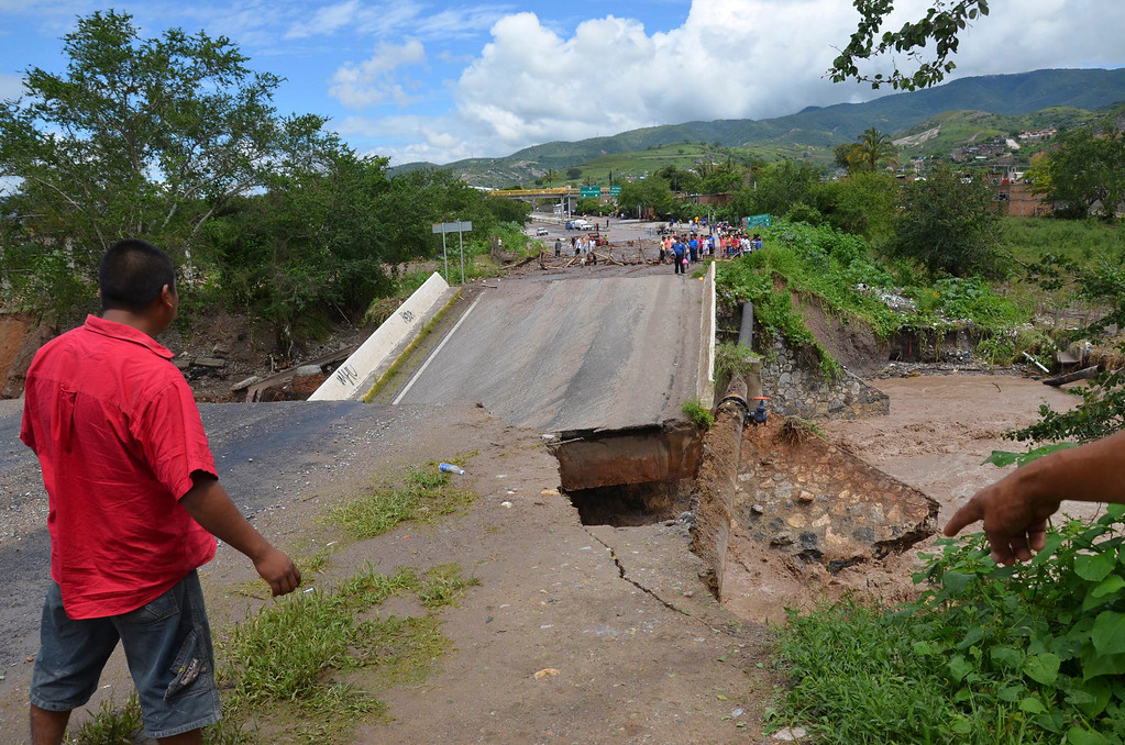 Description of . A man looks at a collapsed bridge over the Huacapa River near the town of Petaquillas, Mexico, Tuesday, Sept. 17, 2013. Twin storms left scenes of havoc on both of Mexico's coasts on Tuesday, with tens of thousands of tourists stranded in resort city of Acapulco on the Pacific and heavy damage reported along the Gulf coast. (AP Photo/Alejandrino Gonzalez)
