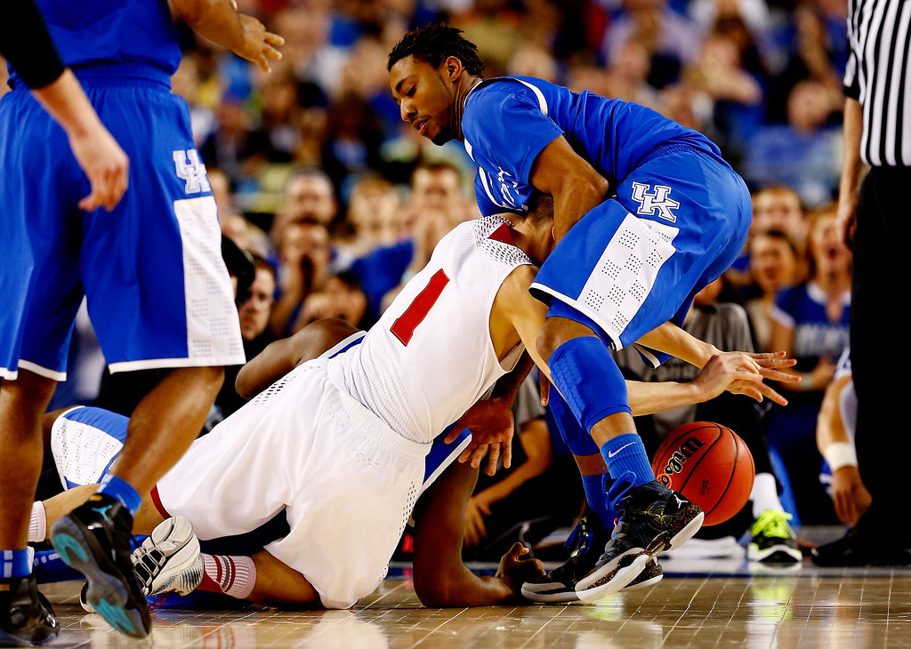 Description of . ARLINGTON, TX - APRIL 05: James Young #1 of the Kentucky Wildcats and Ben Brust #1 of the Wisconsin Badgers battle for a loose ball during the NCAA Men's Final Four Semifinal at AT&T Stadium on April 5, 2014 in Arlington, Texas.  (Photo by Tom Pennington/Getty Images)
