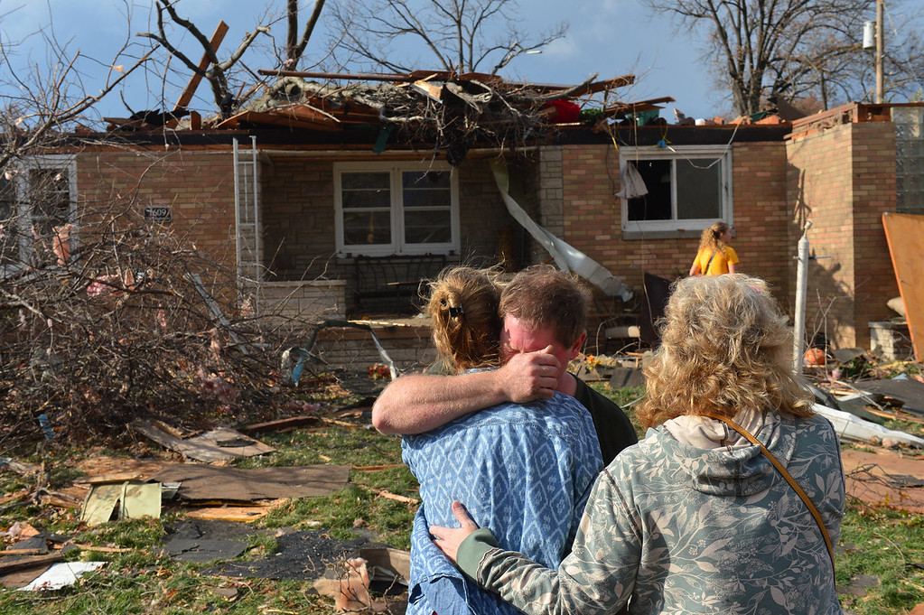 Description of . Ray Baughman embraces family shortly after his home was destroyed by a tornado that left a path of devastation through the north end of Pekin, Il., Sunday, Nov. 17, 2013. Intense thunderstorms and tornadoes swept across the Midwest on Sunday, causing extensive damage in several central Illinois communities while sending people to their basements for shelter. (AP Photo/Journal Star, Fred Zwicky)