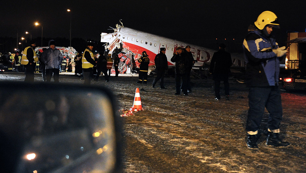 Description of . Russian police investigators and emergency services teams work at the Tu-204 jet crash site near the Vnukovo airport outside Moscow on December 29, 2012. Four people were killed and four were injured when a Russian-made airliner overshot a runway on landing at a Moscow airport and crashed onto a nearby highway, officials said. ANDREY SMIRNOV/AFP/Getty Images