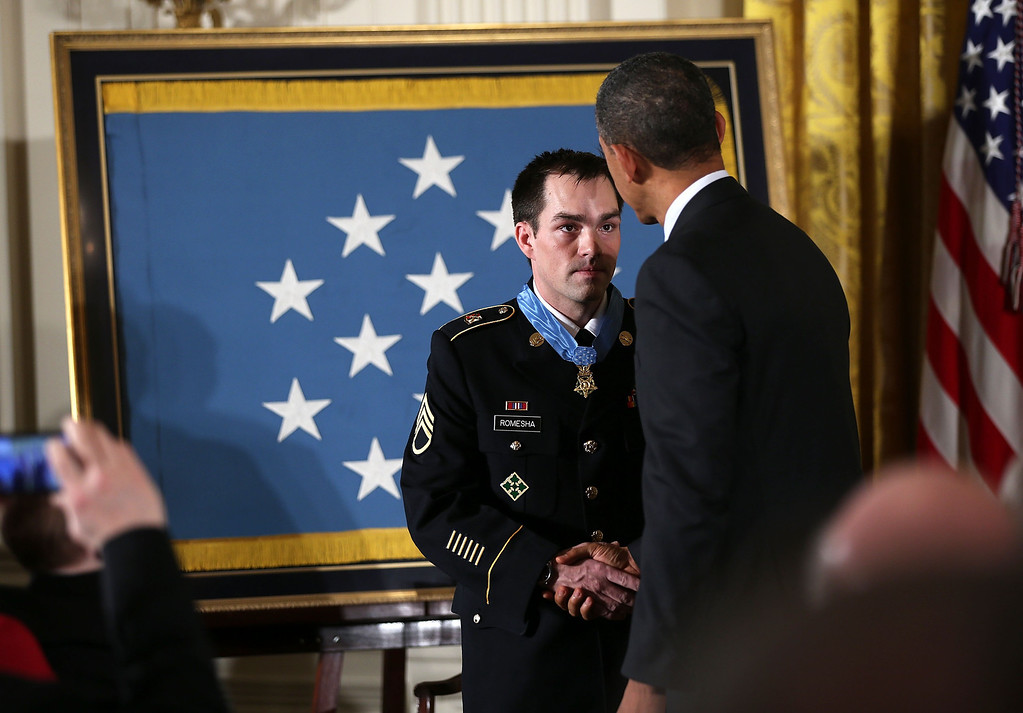 Description of . U.S. President Barack Obama (R) shakes hands with Clinton Romesha (L), a former active duty Army Staff Sergeant, after he presented him with the Medal of Honor for conspicuous gallantry at the White House February 11, 2013 in Washington, DC.  (Photo by Alex Wong/Getty Images)