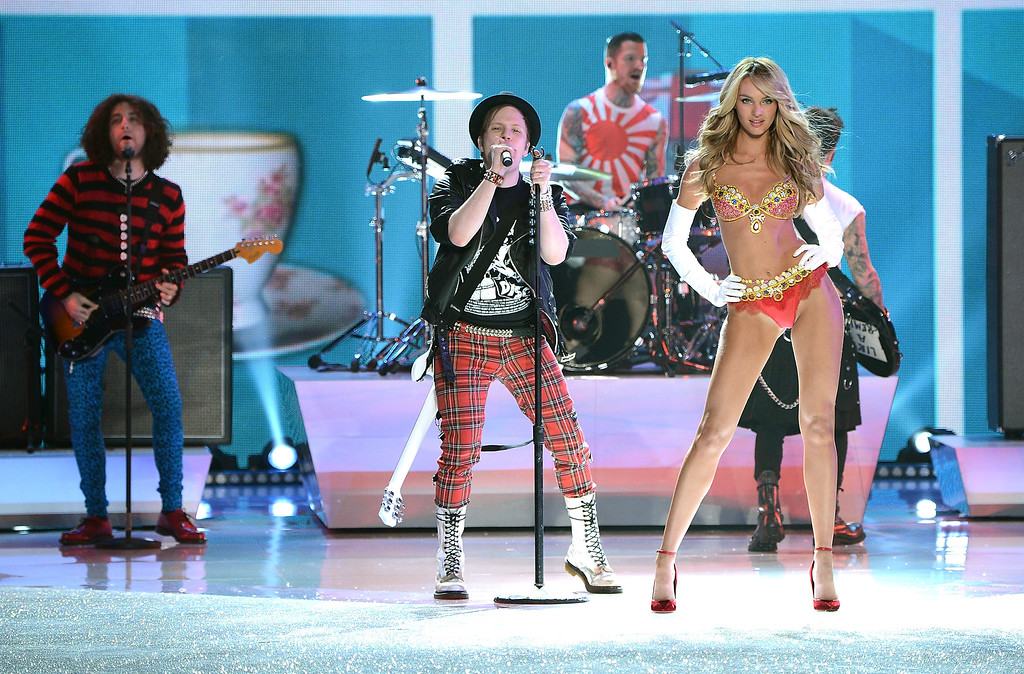 Description of . Fall Out Boy perform while model Candice Swanepoel walks the runway wearing the $10 million Royal Fantasy Bra during the 2013 Victoria's Secret Fashion Show at the 69th Regiment Armory on Wednesday, Nov. 13, 2013 in New York. (Photo by Evan Agostini/Invision/AP)