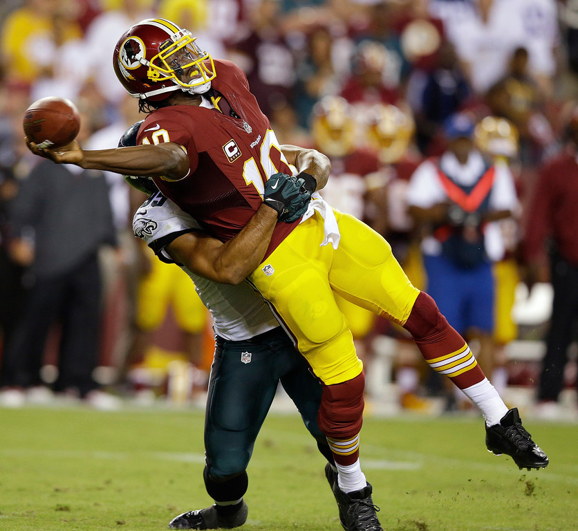 Description of . Washington Redskins quarterback Robert Griffin III (10) tries to get off a pass as he wrapped up by Philadelphia Eagles outside linebacker Mychal Kendricks during the first half of an NFL football game in Landover, Md., Monday, Sept. 9, 2013. (AP Photo/Alex Brandon)